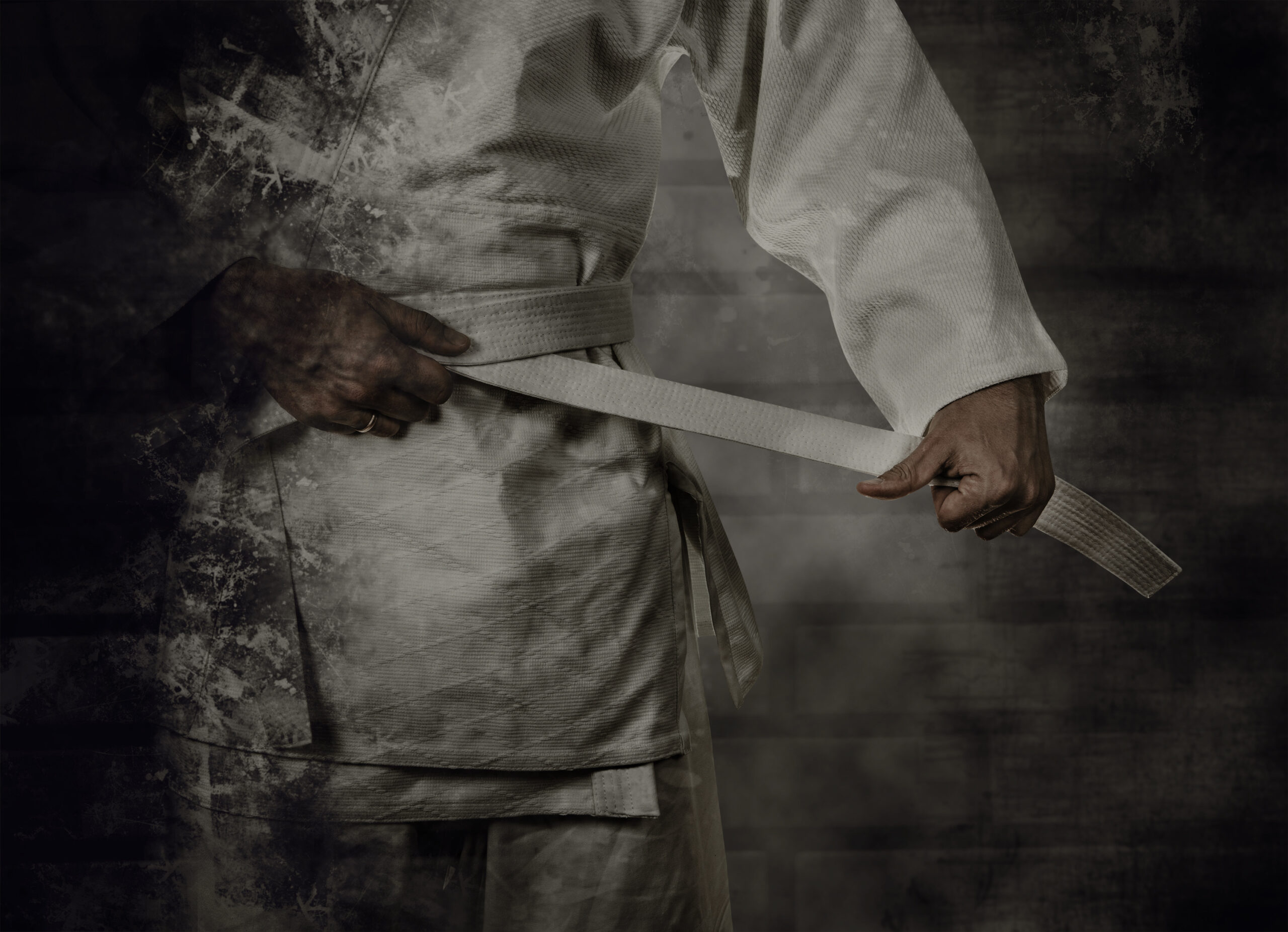 Karateka tying the white belt (obi) with grunge background
